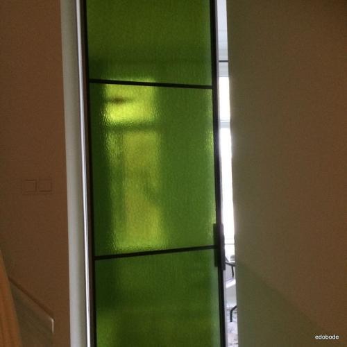 enkele deur met groen gekleur glas.