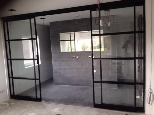 geopende badkamerwand van dubbele schuifdeur met zijlichten