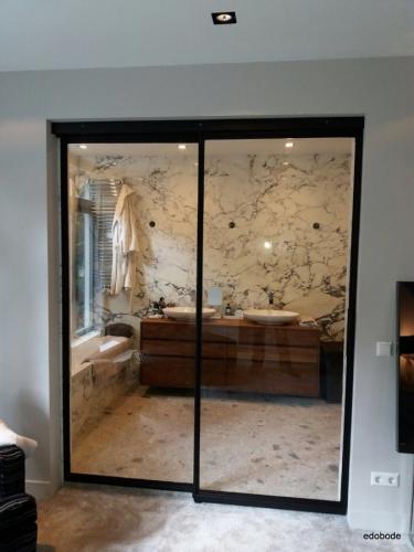 gesloten enkelvlaks schuifdeur met vast zijlicht.. De schuifdeur schuift hier voor het glas in de dag.